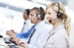 Pretty call centre employee smiling while assisting someone over the phone, with colleagues in background - copyspace